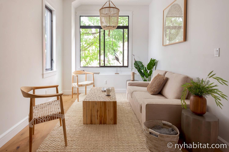 Das Bild zeigt einen Teil des Wohnbereiches in der Mietwohnung NY-17881 mit einem Sofa, Stühlen und einem hölzernen Beistelltisch.