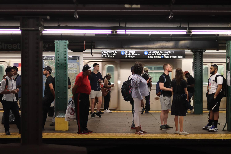 Das Bild zeigt Leute, die auf die New Yorker U-Bahn in einer A/C/E-Station warten.
