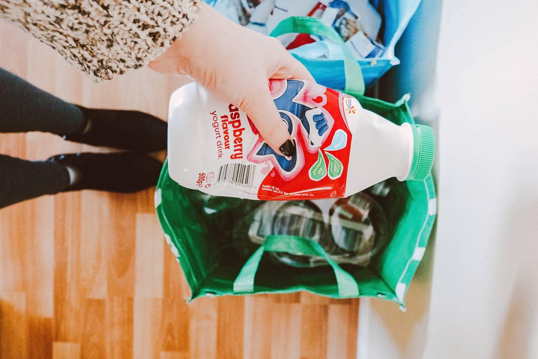 Bild zeigt eine Person, die eine Plastikflasche recycelt.
