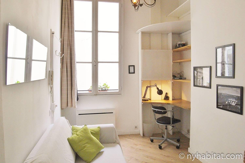 Bild des Wohnbereiches in der Mietwohnung PA-4611 mit einem Sofa und einem Schreibtisch.
