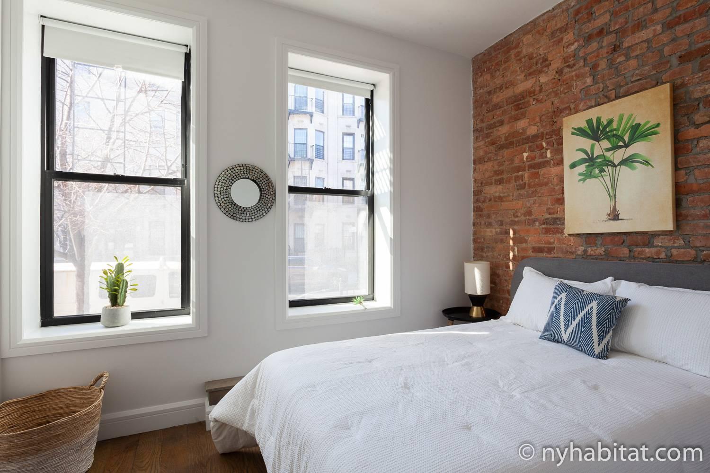 Bild des Schlafzimmers in NY-17871 mit Doppelbett und Kunstwerk.