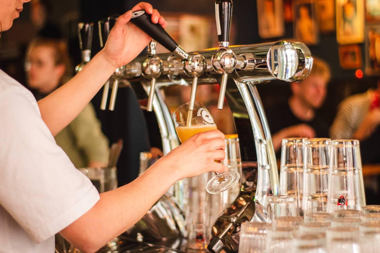 Bild eines Mannes, der Bier vom Zapfhahn zapft.