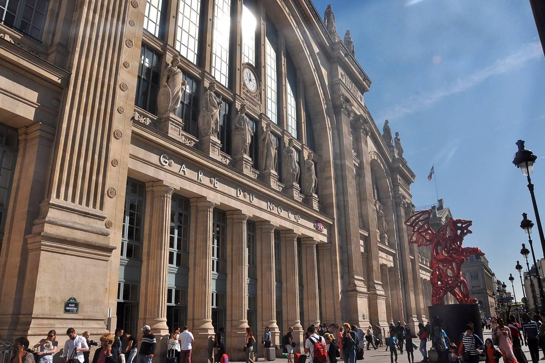Außenansicht des Gare du Nord in Paris mit Passagieren vor dem Bahnhofsgebäude.