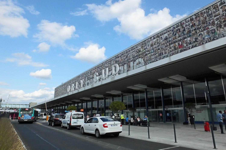 Außenansicht des Terminals 4 des Flughafens Orly mit einem Orlybus am Straßenrand.