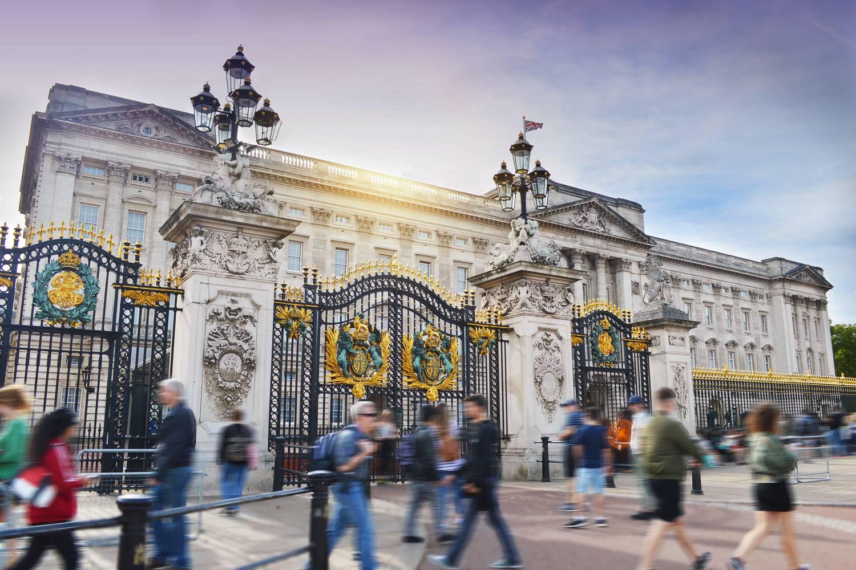 Ein Bild des Buckingham Palace, während Einheimische und Touristen durch die Stadt schlendern.