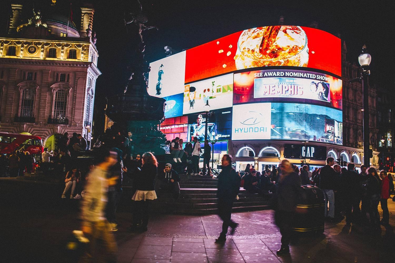 Ein Foto von hellen Neonreklamen und den geschäftigen Straßen des Piccadilly Circus.