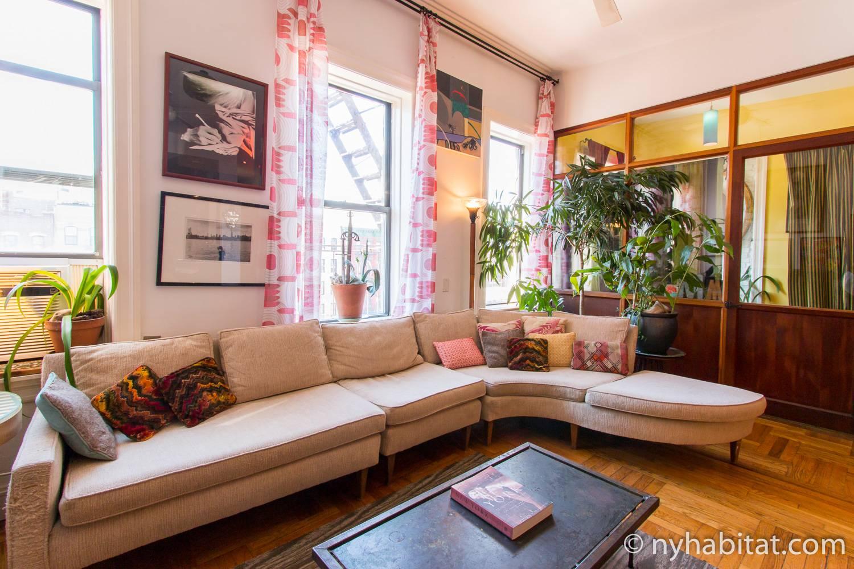 Ein Bild eines Wohnzimmers mit einem zusammensetzbaren Sofa und warmen hervorgehobenen Farbtönen in einer Mietwohnung in der Lower East Side von Manhattan.