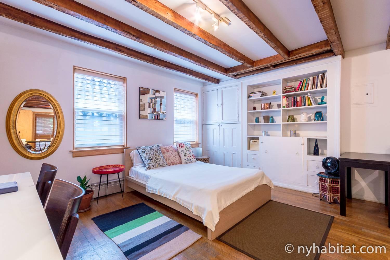 Ein Bild eines Bettes und der eingebauten Bücherregale in einer Studiowohnung (NY-10856) in Williamsburg, Brooklyn.