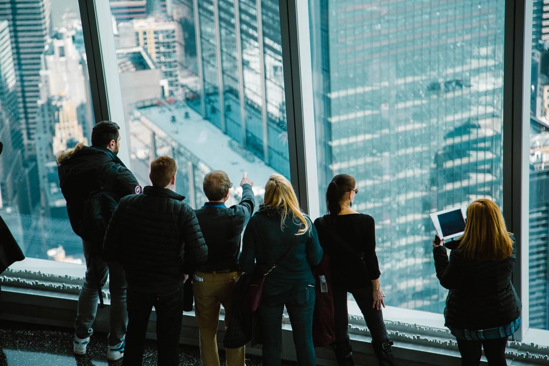 Foto von Besuchern, die aus dem Fenster des One World Obervationsdecks sehen.