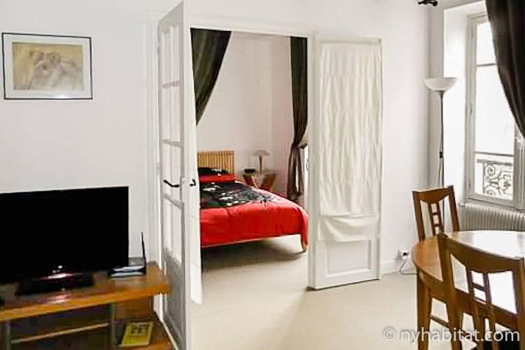 Blick vom Wohnzimmer in das Schlafzimmer der Pariser Wohnung PA-2597 mit Fenstertüren, die die Räume voneinander trennen