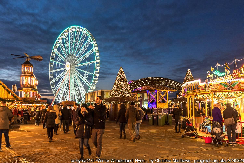 Foto eines leuchtenden Riesenrads, Weihnachtsbäumen und einem Karussell beim jährlichen Festspiel, Winter Wonderland.