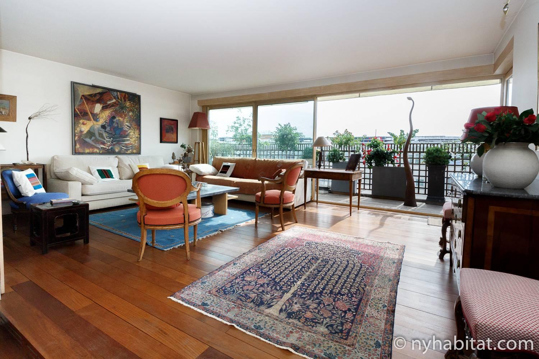 Bild des Wohnzimmers in der möblierten 2-Zimmer-Wohnung zur Miete PA-4706, bei dem ein orangefarbenes Sofa und Stühle und einen Balkon auf der rechten Seite abgebildet ist.