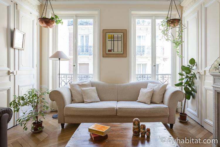 Bild des Wohnzimmers der Ferienwohnung PA-4729 mit einem eleganten weißen Sofa im Vordergrund mit zwei Türen, die im Hintergrund auf den Balkon führen.