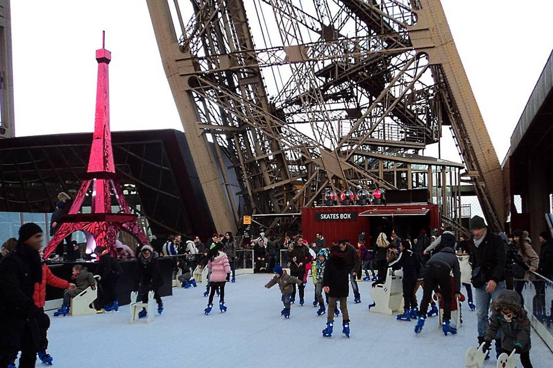 Bild von Menschen beim Eislaufen am Fuße des Eiffelturms.