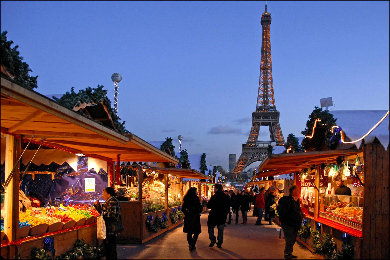 Bild von Holzhütten mit Lebensmitteln und Produkten, die auf einem Weihnachtsmarkt mit dem Eiffelturm im Hintergrund verkauft werden.