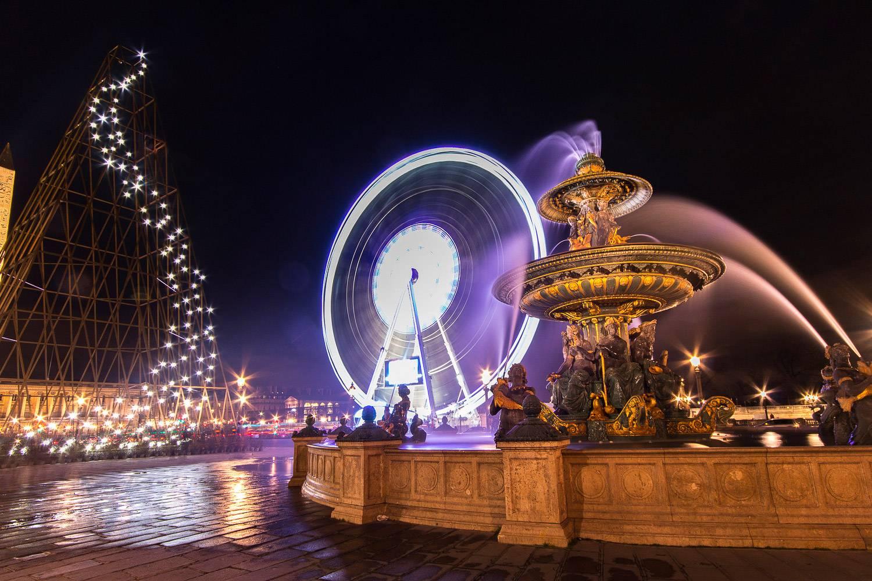 Bild des Place de la Concorde mit Riesenrad, Springbrunnen und Weihnachtsbaum-Aufbau.