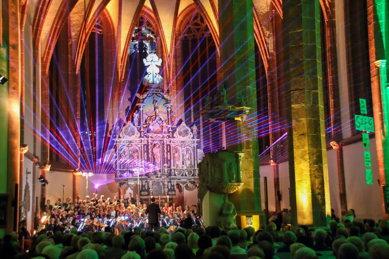 Bild der La Sainte Chapelle während eines Konzerts mit bunten Lichtern, die von der Bühne aus in Richtung des Publikums leuchten.