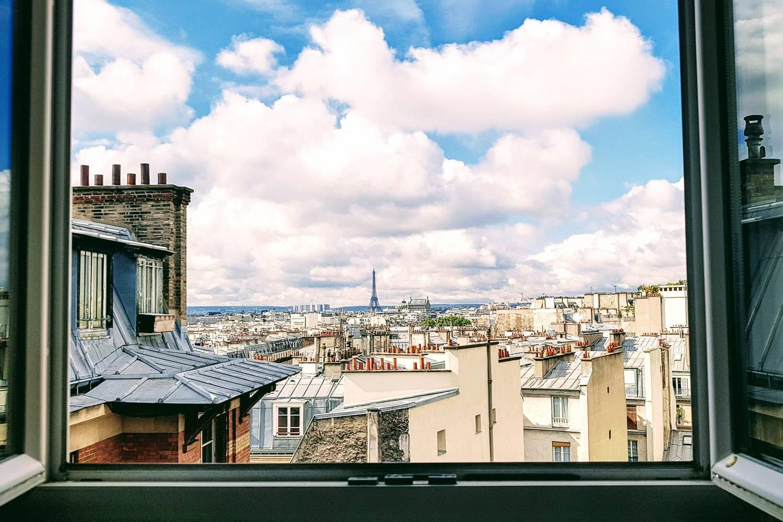 Bild eines offenen Fensters mit Blick auf den Eiffelturm und die Dächer von Paris.