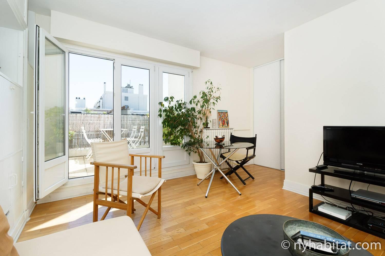 Bild des Wohnbereichs von PA-3384 mit Stühlen, Fernseher und französischen Türen, die auf den Balkon führen.