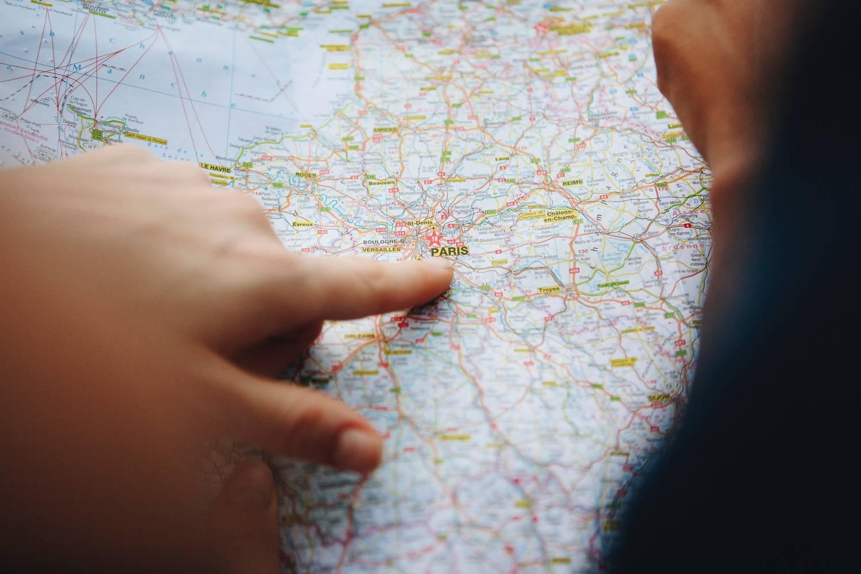 Bild von Händen, die auf eine Karte von Paris zeigen.