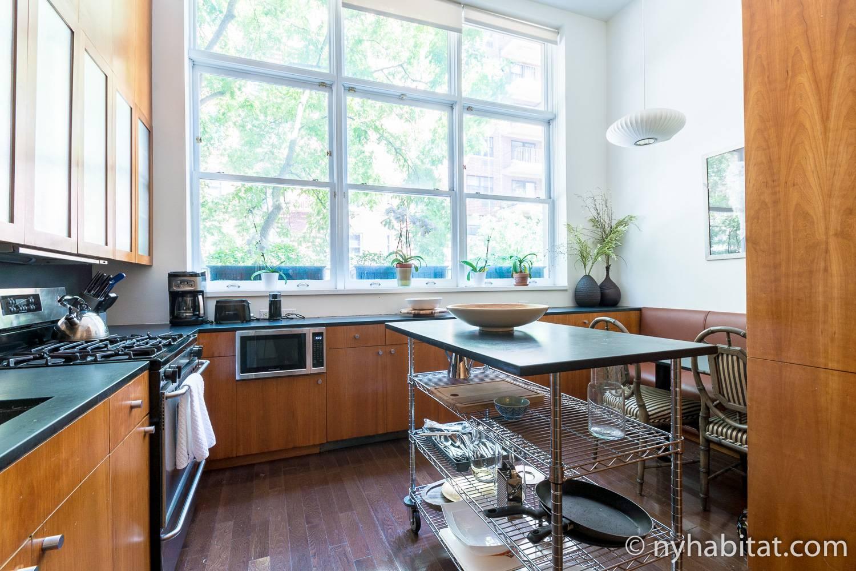 Abbildung der Küche mit einem Ofen, Esstisch und einer mobilen Kücheninsel in Ferienwohnung NY-17637 in der Upper East Side.