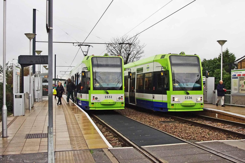 Bild von zwei grünen Straßenbahnen an einer Station.