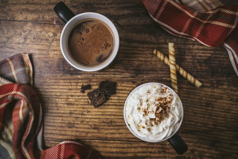 Abbildung von zwei Tassen heißer Schokolade und Keksen. (Foto: Unsplash)