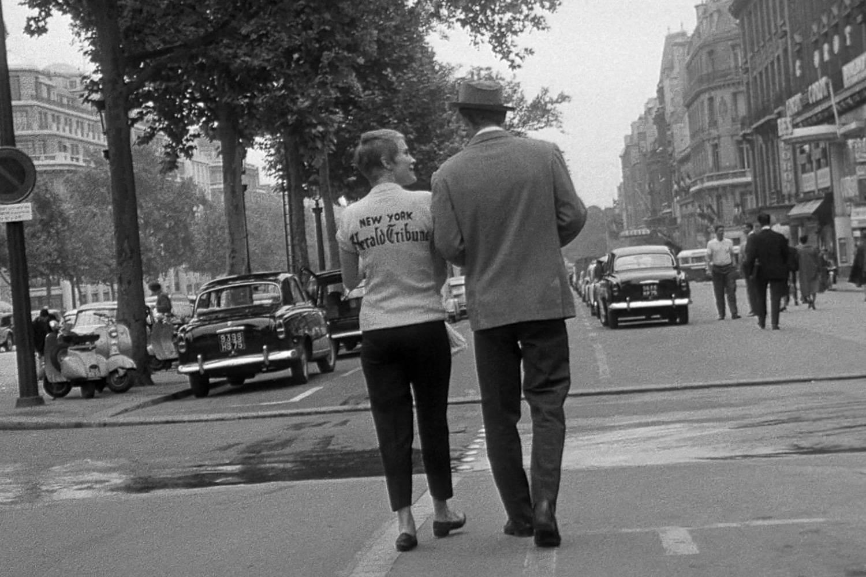 """Schwarzweißbild eines Paars, das die Champs-Élysées in Paris hinunterläuft, aus dem Film """"Breathless"""" von Jean-Luc Godard."""