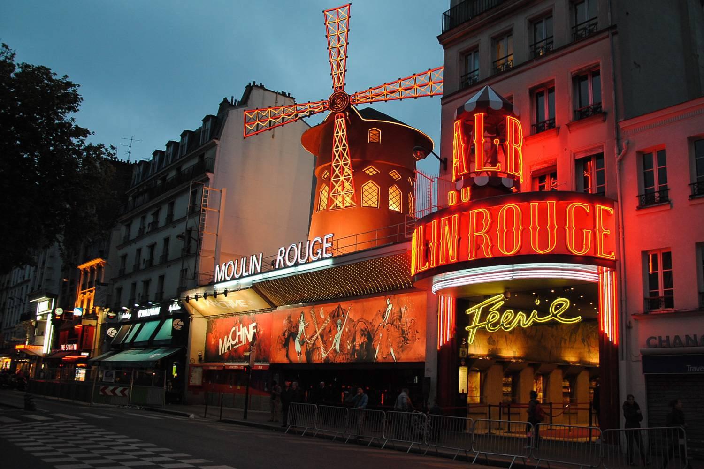 Abbildung der Vorderseite des rot-angestrahlten Moulin Rouges in Paris mit Windmühle. (Foto: Leandro Neumann Ciuffo)