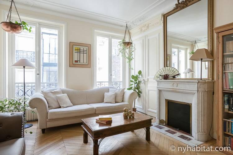 Abbildung des Wohnzimmers der Pariser Ferienwohnung (PA-4729) mit einem antiken Sofa, französischen Fenstern und einem dekorativen Kamin.