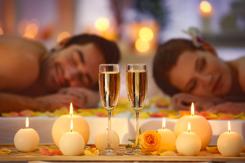 Abbildung eines Paars, das Massagen bekommt, mit Champagner und Kerzen im Vordergrund.