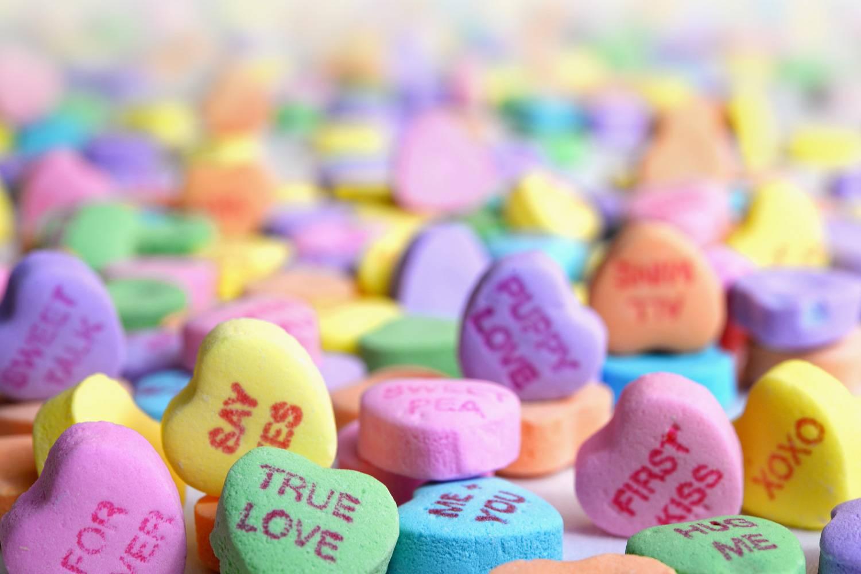 Abbildung von bunten, beschrifteten Valentinstags-Bonbons. (Foto: Unsplash)