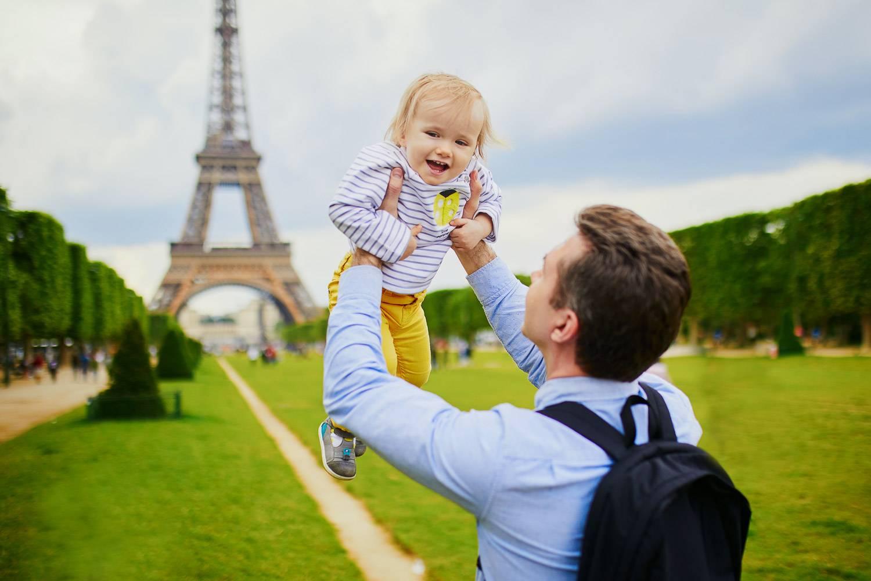 Bild eines Vaters, der sein Baby in der Luft hält mit dem Eiffelturm im Hintergrund