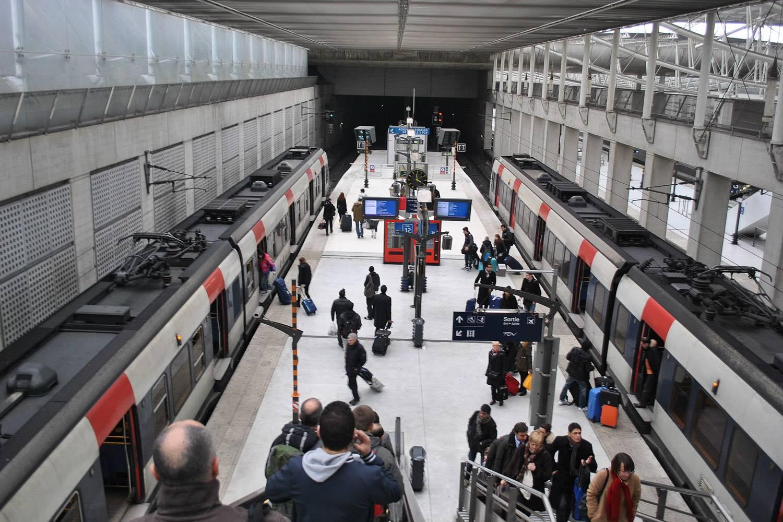 Bild von RER-Zügen und Menschen auf dem Bahnsteig eines Bahnhofes in Paris