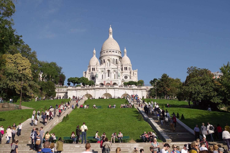 Bild der Sacre Coeur Basilika in Paris mit Menschen, die die Treppen besteigen, die auf den Hügel führen