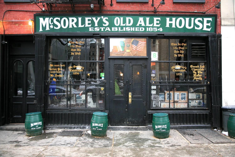 Image de la devanture du pub irlandais McSorley's Old Ale House avec l'inscription « Fondé en 1854 » et des fûts de bière disposés devant