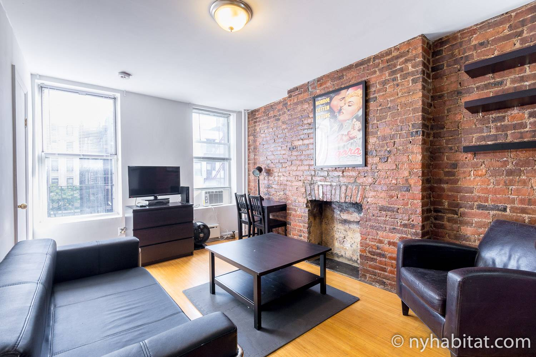 Image du salon de la location meublée NY-17291 située à Little Italy avec ses murs de briques apparentes
