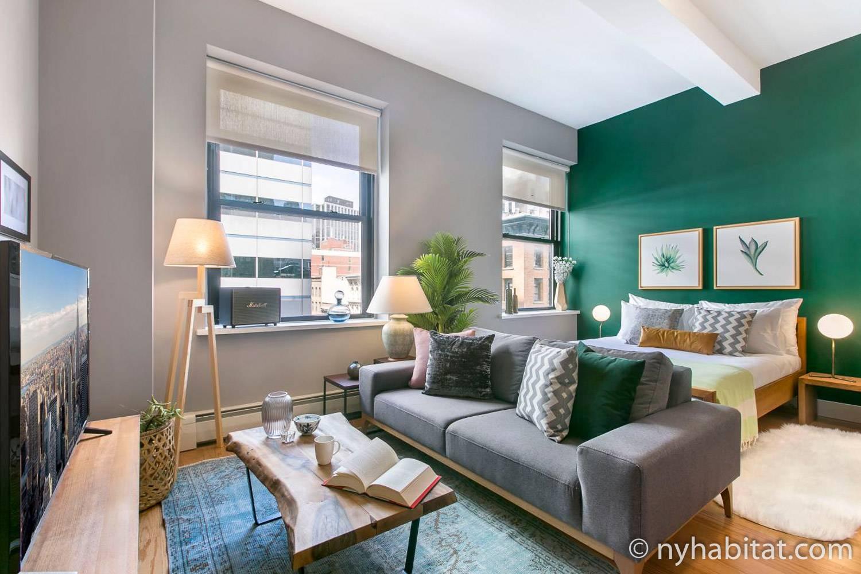 Image du studio meublé NY-17700 à Tribeca avec un canapé et un lit disposés devant un mur vert émeraude