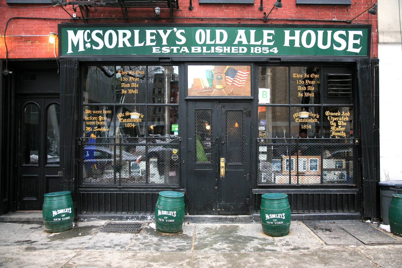 Bild des McSorley's Old Ale House mit einem Schild zur Gründung im Jahr 1854, ein irisches Pub mit Bierfässern vor der Tür