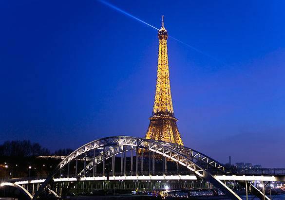 Bild eines leuchtenden Eiffelturms bei Nacht in Paris