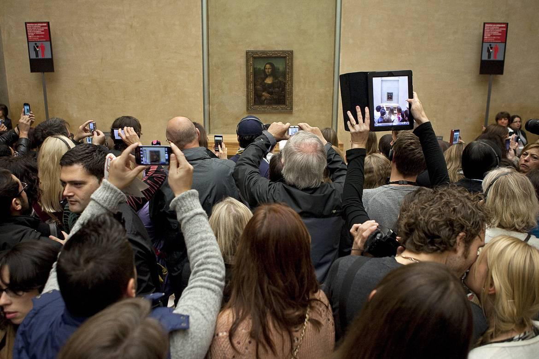 Foto von Gästen, die vor der Mona Lisa im Louvre stehen