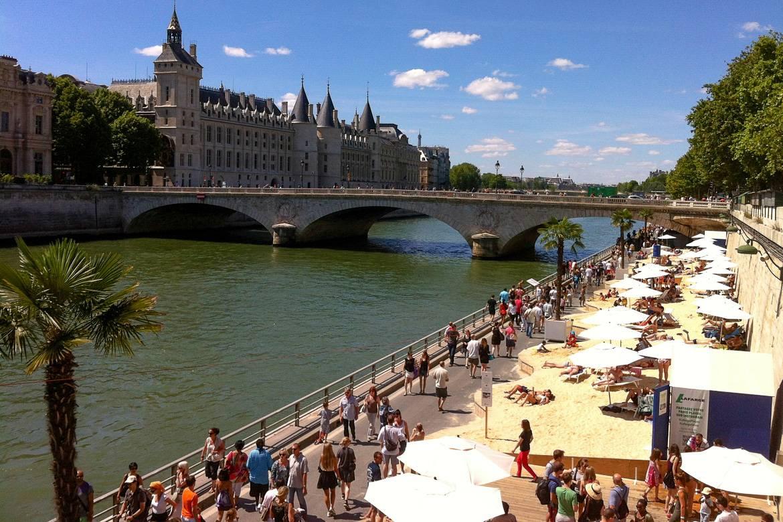 Menschenmengen sammeln sich entlang des künstlichen Strandes während des Monats des Paris Plages