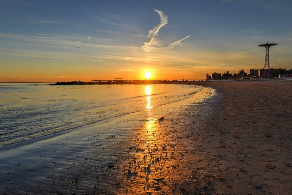 Sonnenuntergang über Coney Island mit den zeitlosen Fahrgeschäften von Luna Park auf der rechten Seite.