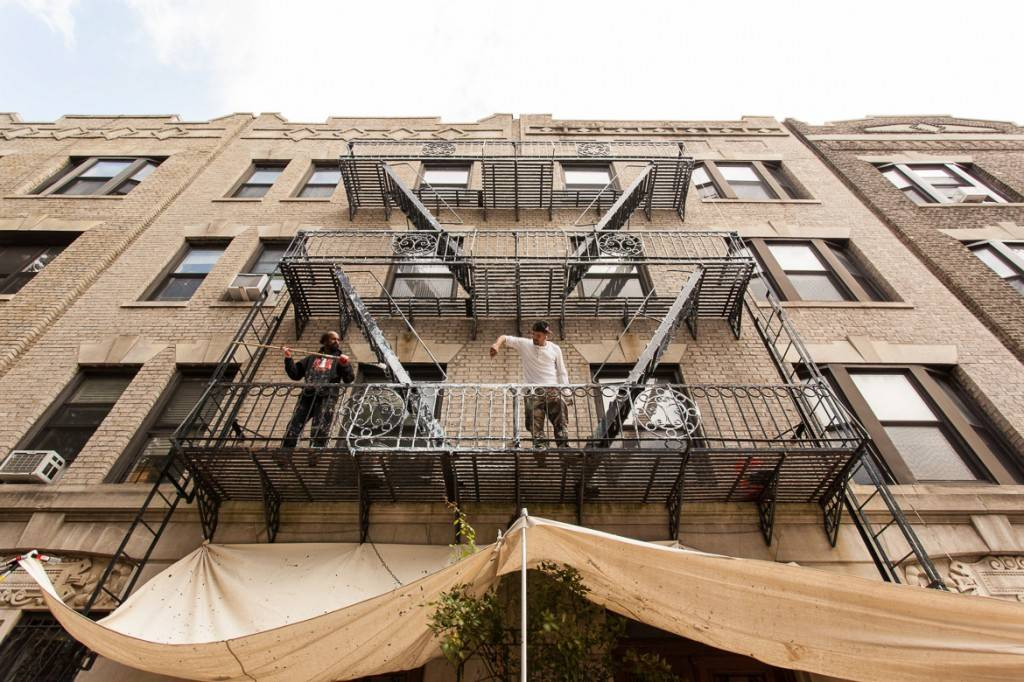 Bild zweier Männer auf der zweiten Etage einer Feuertreppe an einem grauen Gebäude