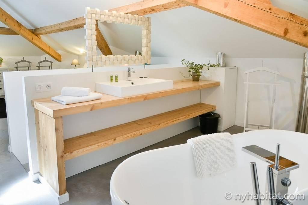 Foto eines Badezimmers mit einer weißen Badewanne und hölzernen Dachbalken