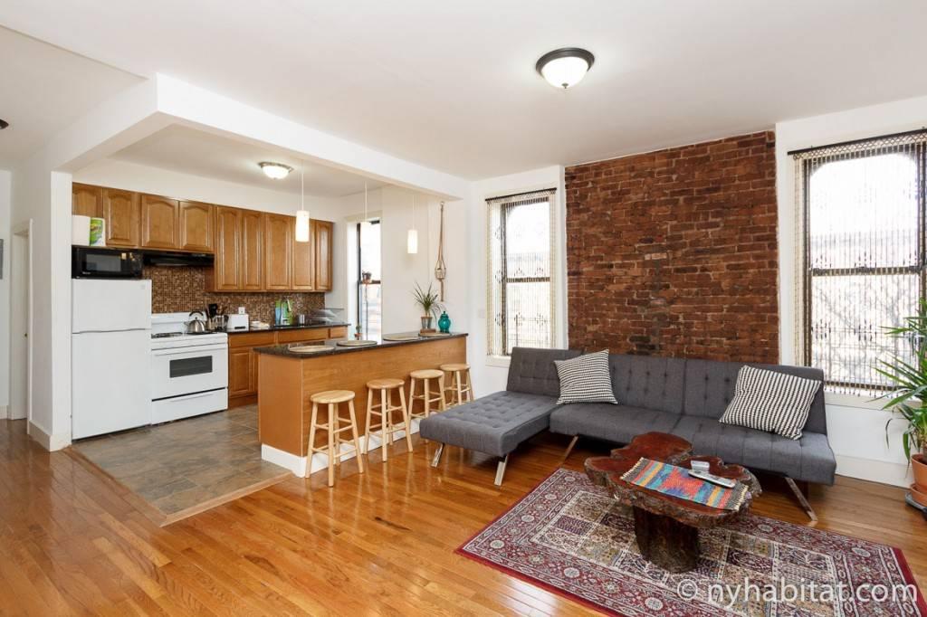 Blick in den Wohnbereich eines Apartments mit einer Küche und freiliegendem Backstein