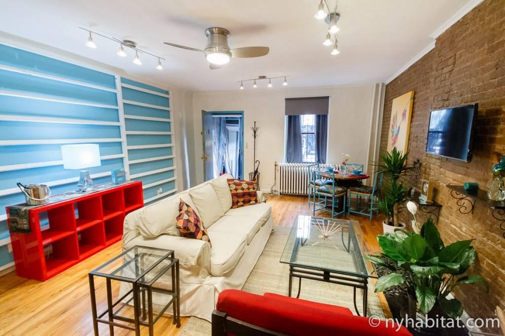 Blick in das farbenfrohe Wohnzimmer eines Apartments und auf eine Backsteinwand