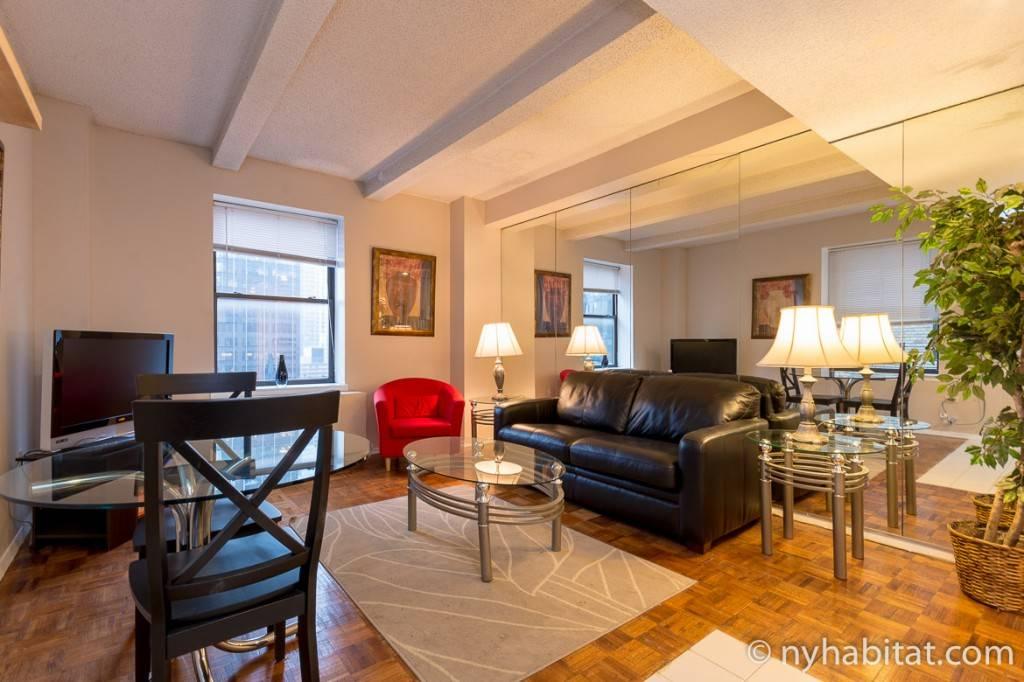 Foto des Wohnbereichs eines Apartments mit einer Couch vor einem Flatscreen-Fernseher