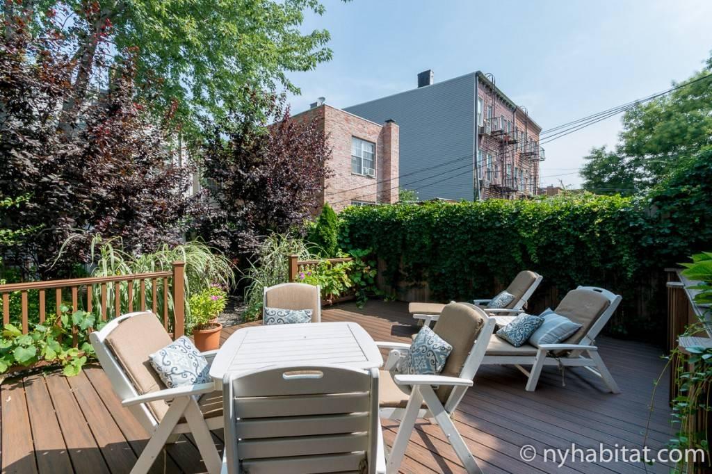Blick auf eine Veranda im Garten mit Liegestühlen an einem sonnigen Tag