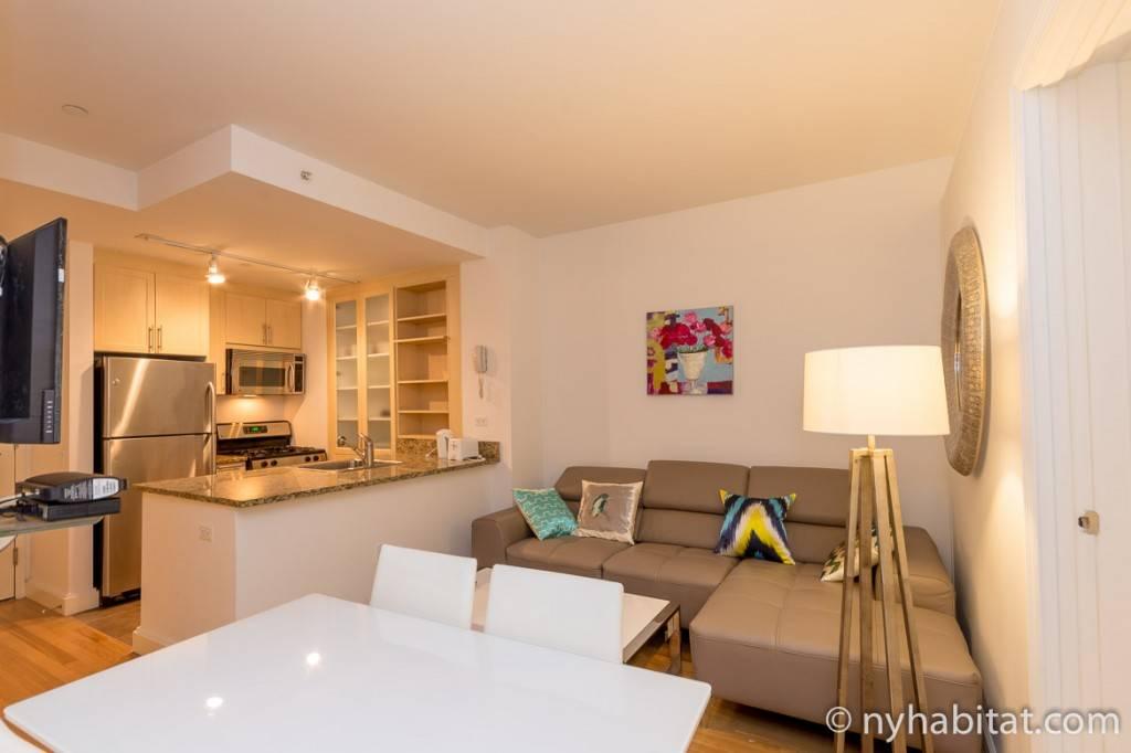 Foto des Wohnbereichs eine Apartments, in dem sich ein rotes Sofa und ein Schreibtisch befinden